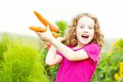 孩子用红萝卜在庭院里 免版税库存图片