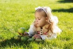 孩子用绿色苹果坐草 库存图片