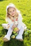 孩子用绿色苹果坐草 免版税库存照片