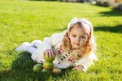 孩子用绿色苹果坐草 图库摄影