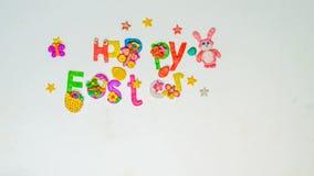 孩子由彩色塑泥和五彩纸屑`愉快的复活节`,行动中止做假日题字 股票录像