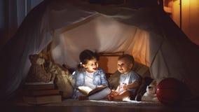 孩子男孩和女孩与手电的阅读书在帐篷 免版税库存照片