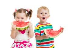 孩子男孩和女孩吃被隔绝的西瓜 免版税库存照片