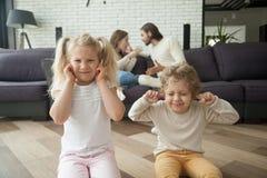 孩子男孩和女孩覆盖物耳朵,父母争论在backgrou 库存图片