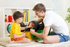 孩子男孩和父亲修理玩具树干 免版税库存照片