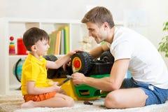 孩子男孩和爸爸修理玩具树干 免版税库存照片