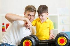 孩子男孩和爸爸修理玩具树干 免版税图库摄影