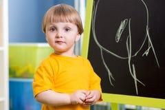 孩子男孩在黑板的粉笔画 免版税库存照片