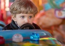 孩子男孩驾驶一辆蓝色汽车在转盘 免版税图库摄影