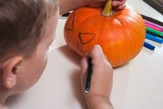 孩子画在南瓜的一张面孔, 库存图片