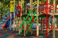 孩子的五颜六色的操场设备在公园 免版税库存照片