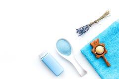 孩子的低变应原的浴化妆用品用淡紫色 瓶、温泉盐、毛巾和玩具在白色背景顶视图 库存图片
