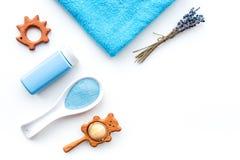孩子的低变应原的浴化妆用品用淡紫色 瓶、温泉盐、毛巾和玩具在白色背景顶视图 免版税库存图片