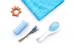 孩子的低变应原的浴化妆用品用淡紫色 瓶、温泉盐、毛巾和玩具在白色背景顶视图 免版税库存照片