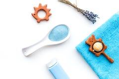 孩子的低变应原的浴化妆用品用淡紫色 瓶、温泉盐、毛巾和玩具在白色背景顶视图 图库摄影