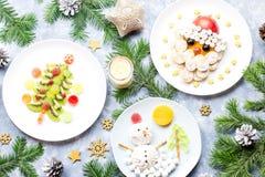 孩子的圣诞节食物-猕猴桃圣诞树,蛋白软糖雪人,香蕉圣诞老人项目 顶视图 免版税库存图片