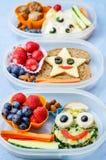 孩子的学校午餐箱子用以滑稽的面孔的形式食物 免版税图库摄影