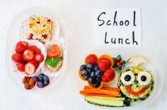 孩子的学校午餐箱子用以滑稽的面孔的形式食物 免版税库存图片