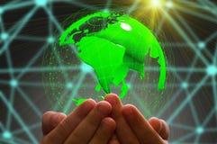 孩子的手在黑暗的背景中的拿着地球 免版税图库摄影