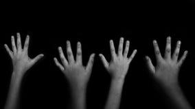 孩子的手在黑背景上升了  免版税库存照片