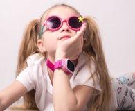 孩子的技术:戴桃红色眼镜的女孩使用一smartwatch 库存照片