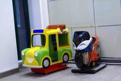 孩子的投入硬币后自动操作的小家伙脚蹬出租汽车和自行车乘驾门的 库存照片
