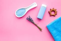 孩子的护肤品用淡紫色 瓶、温泉盐、毛巾和玩具在桃红色背景顶视图复制空间 库存图片