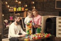 孩子的收养 坐在与五颜六色的建筑砖的桌附近的妈妈、爸爸和孩子 系列组装房子 库存图片