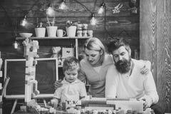 孩子的收养 父母拥抱,观看儿子使用,享受父母身分 家庭休闲概念 父亲,母亲和 免版税库存照片