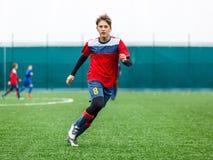 孩子的橄榄球训练 蓝色红色运动服的男孩在足球场 年轻足球运动员滴下并且踢在比赛的球 培训 免版税库存图片