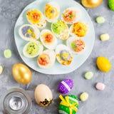 孩子的滑稽的五颜六色的复活节食物与在桌上的装饰 复活节晚餐概念 免版税库存照片