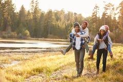 给孩子的父母由湖扛在肩上在步行的乘驾 图库摄影