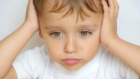 孩子的特写镜头周道地看照相机,握他的在他的头后的手,关闭他的耳朵 孩子 股票录像
