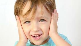 孩子的特写镜头看与喜悦和微笑的照相机,投入他的手对他的头,关闭他的耳朵 股票视频