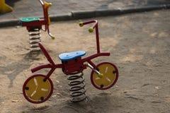 孩子的玩具自行车在操场 免版税库存照片