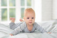 孩子的画象在床上的四个月 免版税库存照片