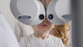 孩子的眼科学诊所-可爱的矮小的白肤金发的女孩检查视觉眼力,关闭  库存照片