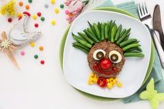 孩子的肉汉堡作为一个逗人喜爱的微笑的小丑 免版税库存图片
