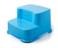 孩子的蓝色凳子立场在背景 免版税库存图片