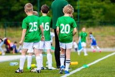 孩子的足球比赛 青年与教练的橄榄球队 男孩当储备球员 免版税图库摄影