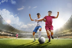 孩子的踢在盛大竞技场的足球 免版税库存图片