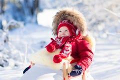 孩子的雪撬和雪乐趣 婴孩sledding在冬天公园 库存图片