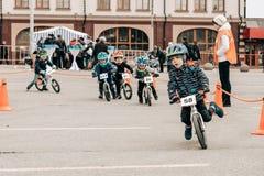 孩子的非职业竞争平衡在列宁广场的自行车 免版税库存图片