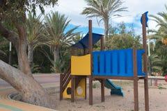 孩子的黄色和蓝色公园戏剧设备有palmtrees的 免版税库存照片