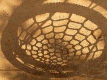孩子的阴影摇摆在橙色沙子上的蜘蛛网 免版税库存照片
