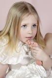 孩子的画象一件白色礼服的有在嘴附近的一只脚的 免版税库存照片