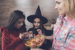 孩子看与兴趣有甜点的花瓶,他们给一个党带来妇女为万圣夜 免版税库存照片