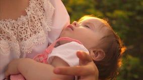 孩子睡着在有太阳金黄光芒的妈妈胳膊  慢的行动 股票录像