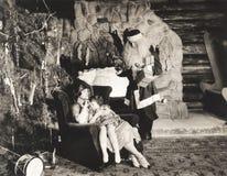 孩子睡着在母亲的膝部当圣诞老人手表 库存照片