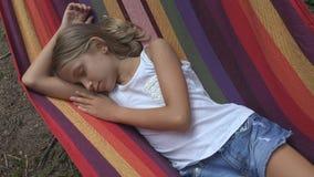 孩子睡觉在野营的吊床的,孩子放松在森林里的,山的女孩 免版税图库摄影
